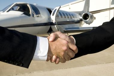 Oameni de afaceri dându-și mâna în fața unui jet de afaceri (Tayhutch © Tayhutch; VisaPro.ca. Toate drepturile rezervate.)